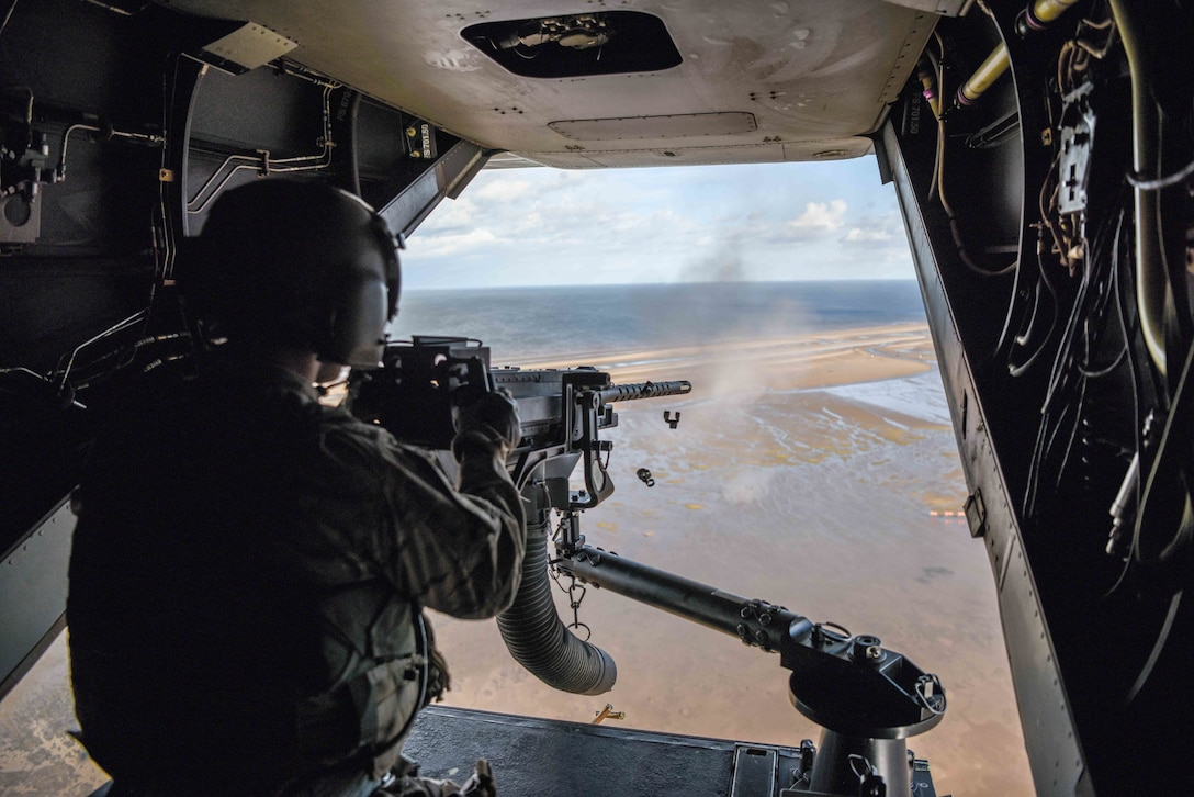 An air commando from the 7th Special Operations Squadron fires a .50 caliber machine gun, aboard a CV-22 Osprey, during a flight around southern England, Sept. 11, 2017. The Osprey flew to a range where the crew sighted, loaded and ran through technical and tactical procedures to re-qualify on the .50 caliber weapons system. (U.S. Air Force photo by Staff Sgt. Philip Steiner)