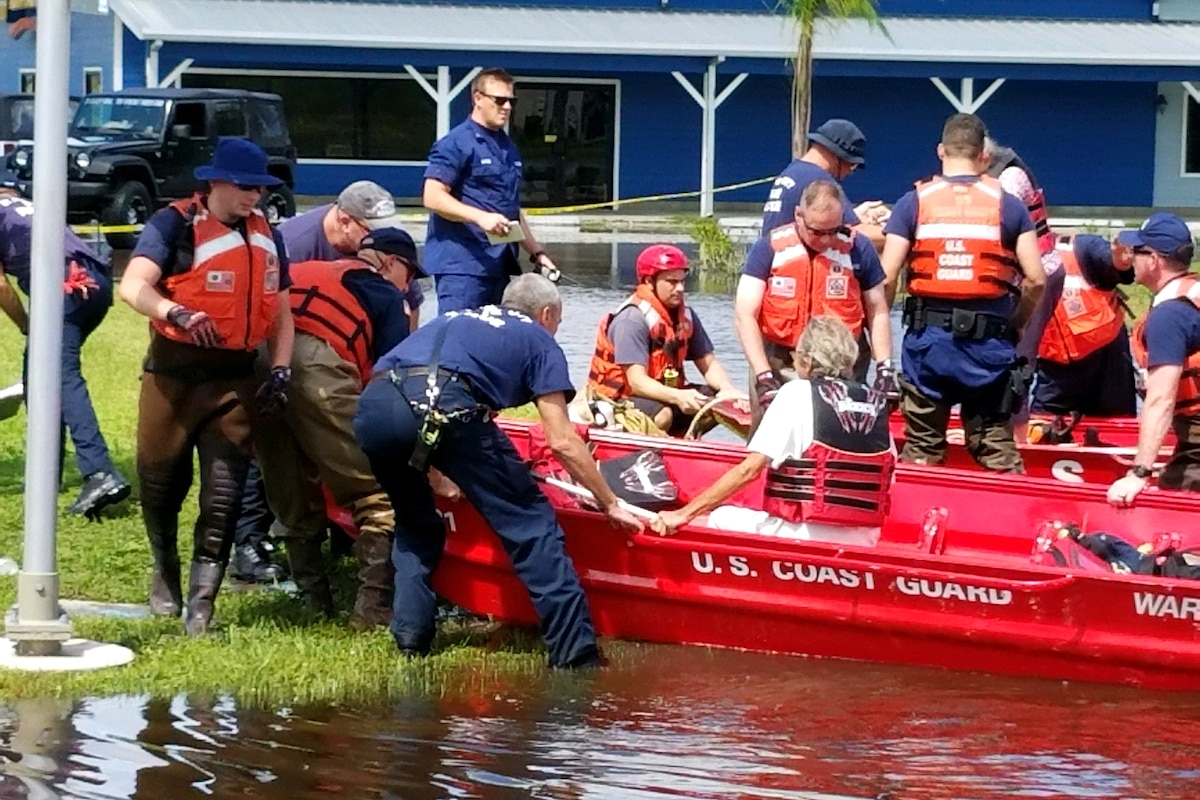Members of the Coast Guard assist civilians into boats.