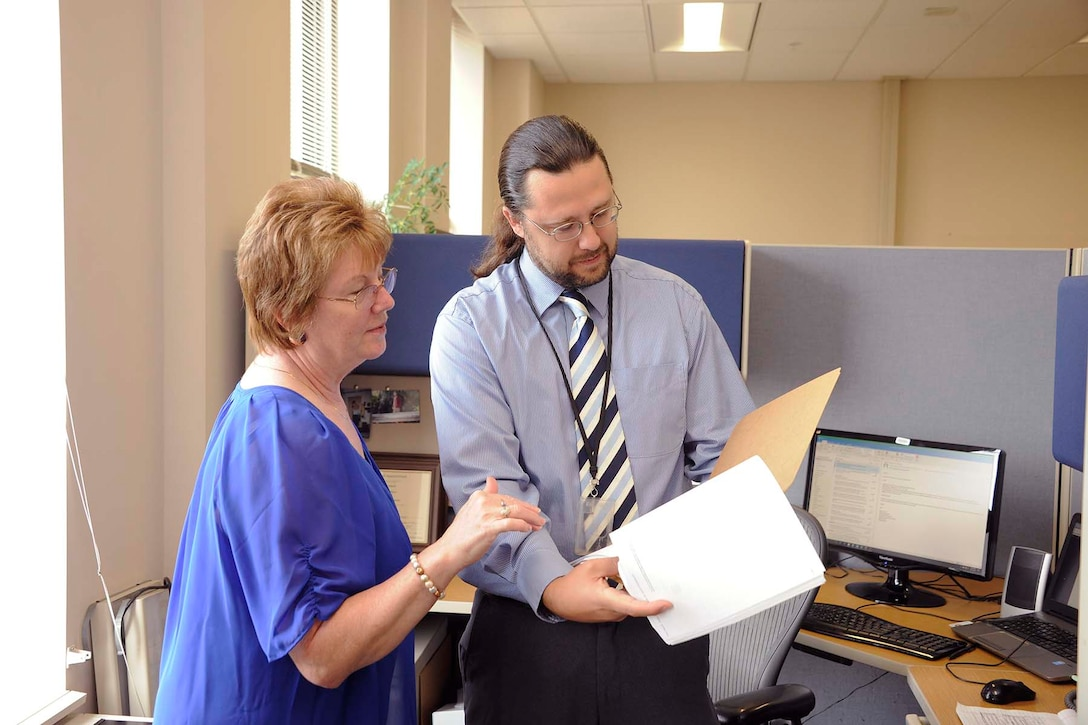 Robert Steed, a contracting officer for DLA Disposition Services, discusses the new contract with Sheryl Woods, DLA Disposition Services' special assistant for small business.