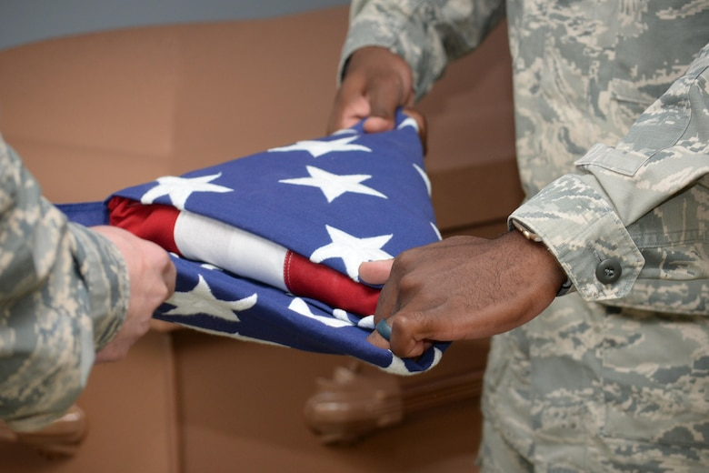 Columbus Air Force Base Honor Guardsmen practice folding the American flag into the traditional tri-fold Sept. 12, 2017, on Columbus Air Force Base, Mississippi. Guardsmen need to ensure the flag is folded neatly in order to present it to the family of a deceased veteran. (U.S. Air Force photo by Airman 1st Class Beaux Hebert)