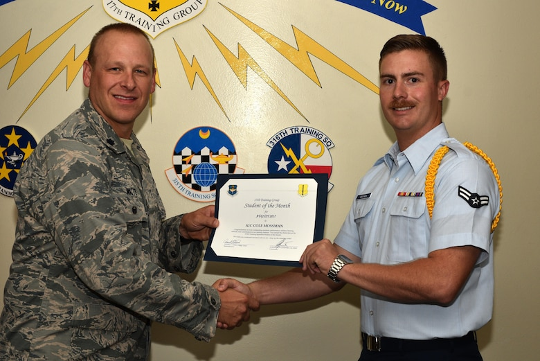 U.S. Air Force Lt. Col. Steven Watts, 17th Training Group Deputy commander, presents the 315th Training Squadron Student of the Month award for August 2017 to Airman 1st Class Cole Mossman, 315th Training Squadron student, at Brandenburg Hall on Goodfellow Air Force Base, Texas, Sept. 8, 2017. (U.S. Air Force photo by Senior Airman Scott Jackson/Released)