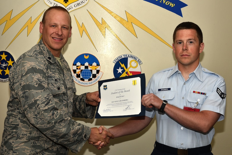 U.S. Air Force Lt. Col. Steven Watts, 17th Training Group Deputy commander, presents the 312th Training Squadron Student of the Month award for August 2017 to Airman 1st Class Kyle Gruenberg, 312th Training Squadron student, at Brandenburg Hall on Goodfellow Air Force Base, Texas, Sept. 8, 2017. (U.S. Air Force photo by Senior Airman Scott Jackson/Released)