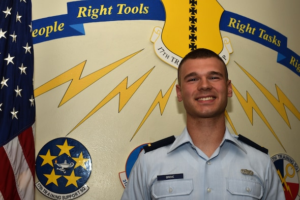 U.S. Air Force 2nd Lt. Garrett Grove, 315th Training Squadron student, stands before the 17th Training Group emblem at Brandenburg Hall on Goodfellow Air Force Base, Texas, Sept. 8, 2017. Grove is the Goodfellow Student of the Month spotlight for August 2017, a series highlighting Goodfellow students. (U.S. Air Force photo by Senior Airman Scott Jackson/Released)