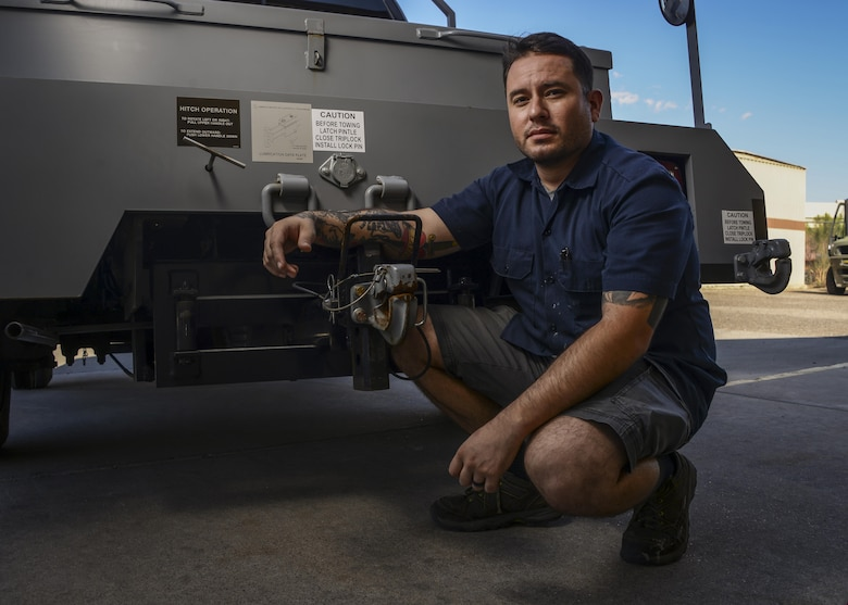 Daniel Villela, 56th Logistics Readiness Squadron mobile equipment mechanic, poses for a portrait next to the pintle hook assembly on a bobtail Sept. 14, 2017 at Luke Air Force Base, Ariz. Villela was the lead mechanic to provide the steps in reconfiguring and implementing a fix to the pintle hook mechanism for the bobtails that tow the F-35 on the flightline at Luke. (U.S. Air Force photo/Airman 1st Class Caleb Worpel)