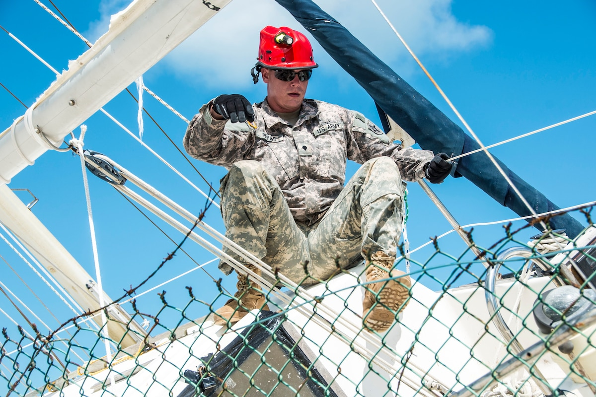 A soldier climbs on top of a sailboat lodged in a fence.
