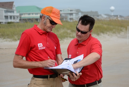 Coastal engineers Doug Wall, left, and Kevin Conner refer to a Preliminary Damage Assessment (PDA) notebook on Wrightsville Beach during their spot checks of specific sections of the beach. They uploaded data to the District's GIS server to be analyzed for any potential damage. (USACE photo by Hank Heusinkveld)