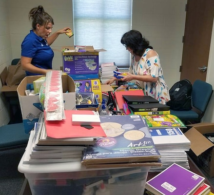 Dr. Jill Blankenship, principal of Blaschke Sheldon Elementary in the Ingleside Independent School District and Sylvia Elizondo, the superintendent's administrative assistant, open supplies donated by Robert G. Cole Middle and High School at Joint Base San Antonio-Fort Sam Houston.