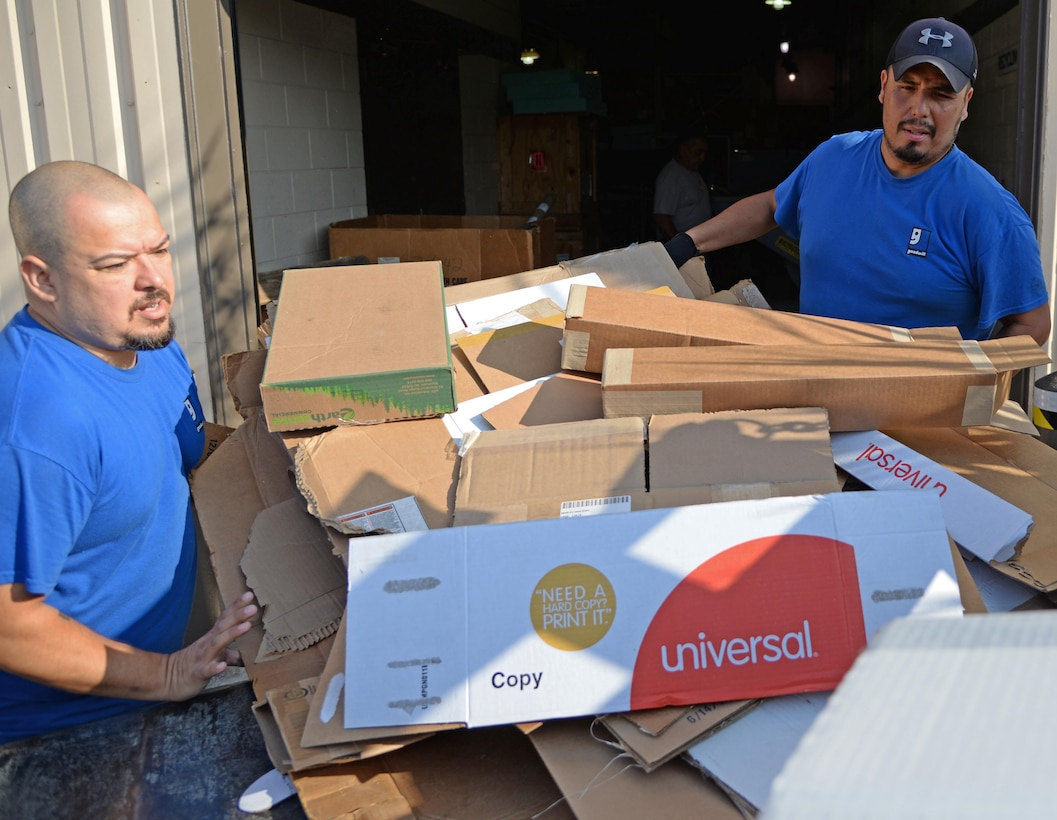 Mike Cardenas and Roland Deleon, Laughlin Air Force Base, Texas recyclers, tosses cardboard into a flatbed at the aircraft engine workshop here Sept. 15, 2017. Cardenas and Deleon, who both are prior service members, have more than 20 years' combined experience in recycling at the facility.