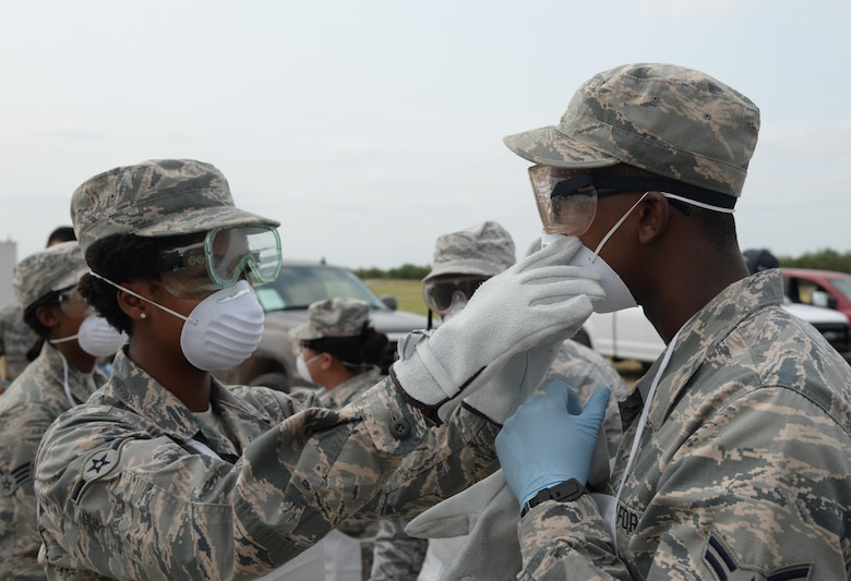 Airman Brittany Zipperian assists Airman 1st Class Daud Mohamad with a face mask during the Scarlet Hawk Exercise 17-03 at Laughlin Air Force Base, Texas, Sept. 6, 2017. While in the search and recovery phase of the exercise, the team donned personal protective gear, which would protect them from blood-borne pathogens. Both Zipperian and Mohamd are members of the 47th Force Support Squadron.