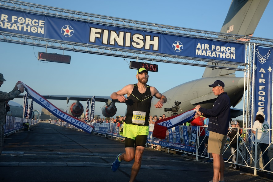 Dustin Sprague crosses the finish line as the overall men's winner of the 10K race at the 21st running of the 2017 U.S. Air Force Marathon at Wright-Patterson Air Force Base on Sept. 16.  Sprague, from Dayton, Ohio, finished with a time of 33:04.  (U.S. Air Force photo / R.J. Oriez)