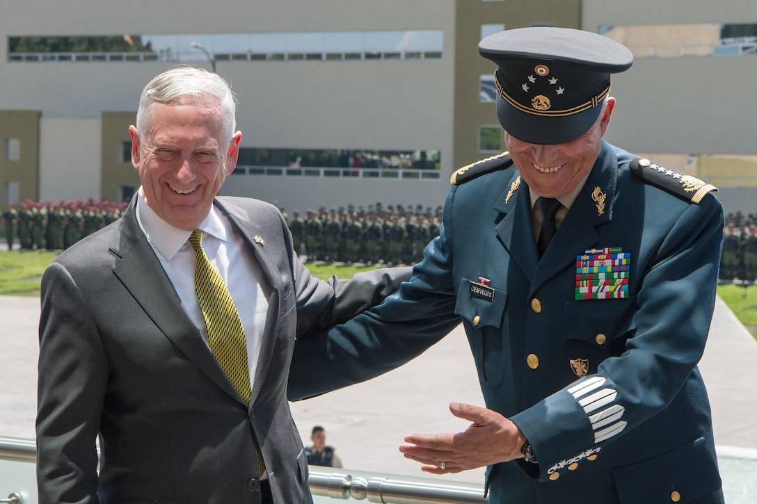 U.S. and Mexican defense leaders laugh together.