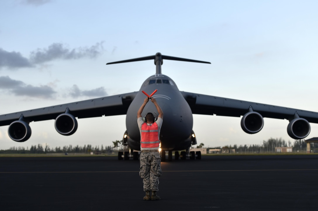 Staff Sgt. Ozzie Slawnikowski, 921st Contingency Response Squadron crew chief, marshals a C-5M Super Galaxy, Sep. 16, 2017, at Homestead Air Reserve Base, Fla. A 17-member contingency response team from the 821st Contingency Response Group from Travis Air Force Base, Calif., deployed to Homestead Air Reserve Base, Fla., to augment the 439th Airlift Wing airfield capabilities in support of Hurricane Irma relief efforts. (U.S. Air Force photo by Tech. Sgt. Liliana Moreno/Released)
