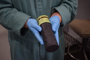A scientist holds an obsolete grenade,