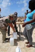 Anne Galegor, a representative of the Office of Foreign Disaster Assistance, helps a U.S. service member with Joint Task Force - Leeward Islands fill up water jugs