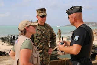 Anne Galegor, a representative of the Office of Foreign Disaster Assistance, and U.S. Marine Col. Michael V. Samarov, the commander of Joint Task Force - Leeward Islands, speak with a member of the Saint Martin National Gendarmerie at a water distribution site