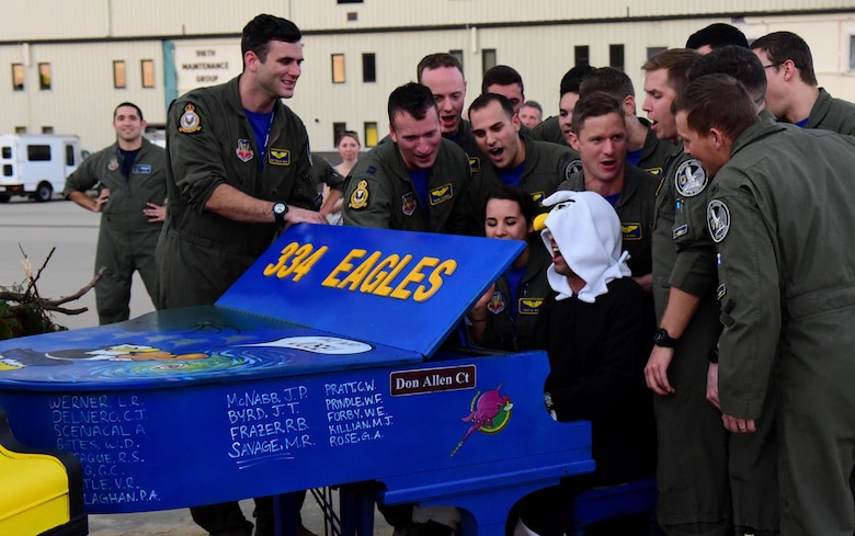 Members of the 334th Fighter Squadron sing together while a fellow Eagle plays their decorated piano during the 4th Fighter Wing Battle of Britain celebration, Sept. 15, 2017, at Seymour Johnson Air Force Base, North Carolina.
