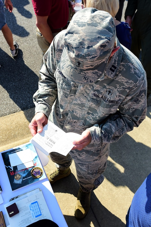 Capt. Douglas Dixon, 4th Fighter Wing chaplain, looks through a Bible taken out of the 1992 time capsule, Sept. 15, 2017, at Seymour Johnson Air Force Base, North Carolina. The capsule contained mementos from 1967, 1992, and will contain new items before being buried for another 25 years. (U.S. Air Force photo by Airman 1st Class Kenneth Boyton)