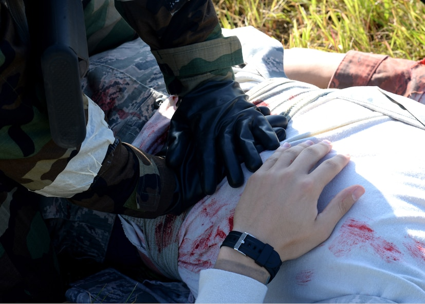 Staff Sgt. Garriel Viera, 51st Security Forces defender, left, applies pressure to an abdominal wound of Airman 1st Class Steven May, 51st Medical Group medical technician, during a mass casualty scenario of exercise Beverly Herd 17-3 at Osan Air Base, Republic of Korea September 18, 2017. The scenario was designed to examine medical personnel's and first responders' ability to apply self-aid and buddy care on-scene and treat a number of casualties in an emergency. (U.S. Air Force photo by Tech Sgt. Ashley Tyler/Released)