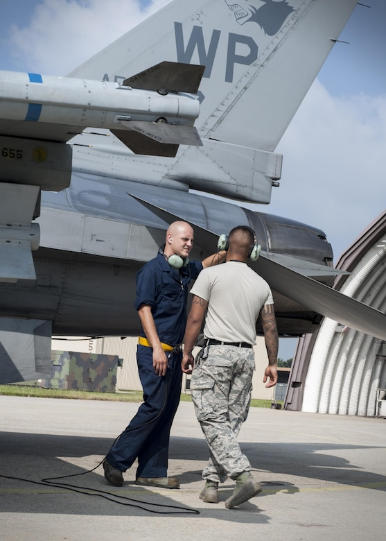 """U.S. Air Force Staff Sgt. Eugene Travis, 8th Air Maintenance Squadron crew chief, briefs Airman 1st Class Anthony Martinez, 8th Security Forces Squadron defender, while participating in the """"Job Swap"""" event at Kunsan Air Base, Republic of Korea, Sept. 12, 2017. The week-long event was to give 8th SFS defenders a better look at the assets that they are protecting day in and day out. (U.S. Air Force photo by Staff Sgt. Victoria H. Taylor)"""