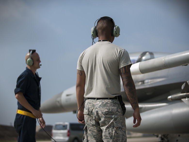 """U.S. Air Force Staff Sgt. Eugene Travis, 8th Air Maintenance Squadron crew chief, and Airman 1st Class Anthony Martinez, 8th Security Forces Squadron defender, prepare to launch a jet while participating in the """"Job Swap"""" event at Kunsan Air Base, Republic of Korea, Sept. 12, 2017. Travis taught Martinez the basic functions of the aircraft so that he can better understand the assets that he and other 8th SFS defenders are protecting day in and day out. (U.S. Air Force photo by Staff Sgt. Victoria H. Taylor)"""