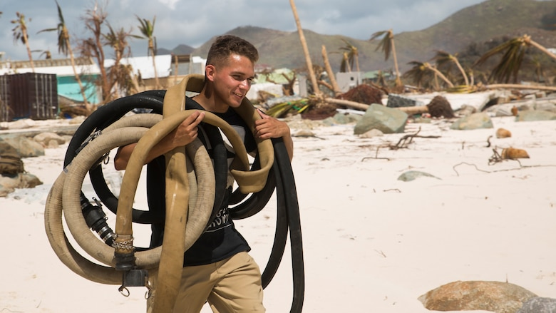 U.S. Marine Lance Cpl. Dakota Medina, a landing support specialist with Joint Task Force - Leeward Islands, carries hoses belonging to a Lightweight Water Purification System from a box truck at Orient Beach, Saint Martin, Sept. 16, 2017. The Marines arrived to assess possible locations to set up their LWPS in order to produce potable water for communities on the island most affected by Hurricane Irma. At the request of partner nations, JTF-LI deployed aircraft and service members to areas in the eastern Caribbean Sea impacted by the storm. The task force is a U.S. military unit composed of Marines, Soldiers, Sailors, and Airmen, and represents U.S. Southern Command's primary response to Hurricane Irma.