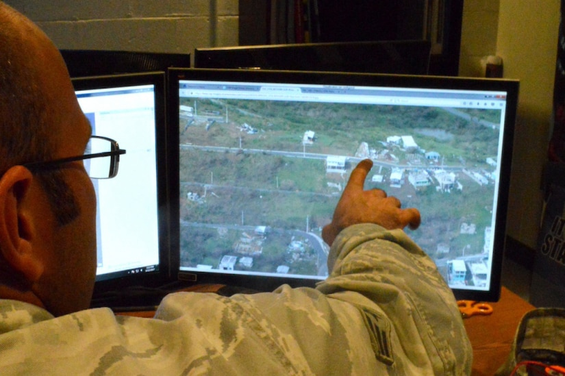 A man points at a computer screen.