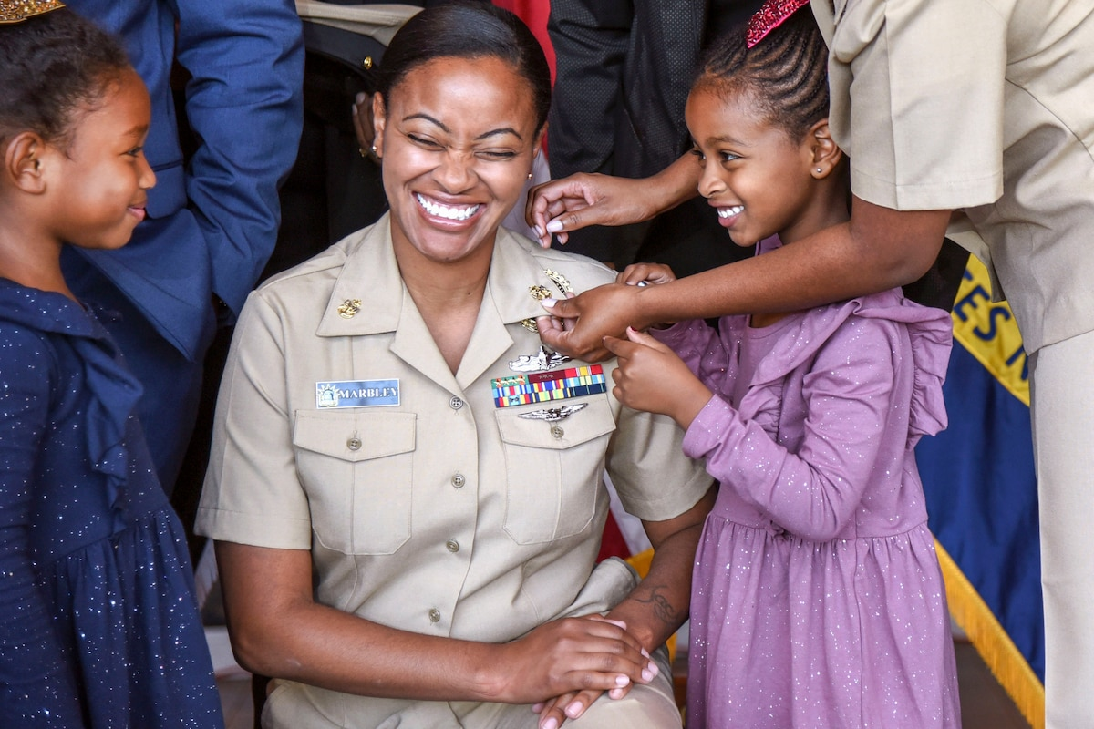 A woman kneels and smiles while a girl helps pin anchors to her uniform collar.