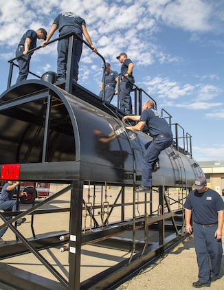 Firefighters with Fire and Emergency Services climb aboard their new three-domed railcar training simulator, created by Advanced Entertainment Technologies, during a training exercise aboard Marine Corps Logistics Base Barstow, Calif., Aug. 30. The simulator offers several realistic training situations to help ensure that firefighters are prepared for potential railway emergencies on base or within the local area.