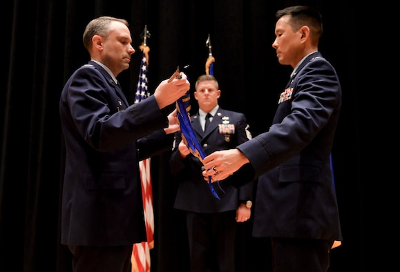 Col. Donald Wilson, Air and Cyberspace Intelligence Group commander, and Lt. Col. Burt Okamoto, Integrated Command Control Communication Computers Intelligence Surveillance Reconnaissance Analysis Squadron commander, reveal the new ACX guidon during a re-designation ceremony Sept. 8, at the National Air and Space Intelligence Center.