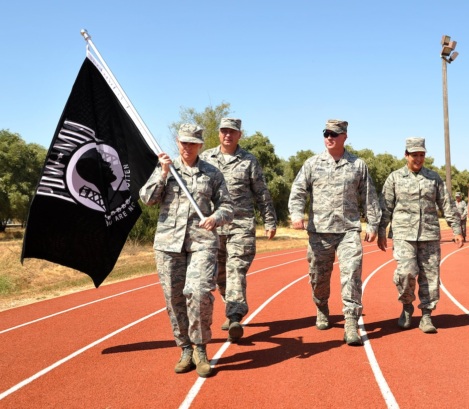 Chief Master Sgt. Jessica Bender, 9th Reconnaissance Wing command chief, carries a POW/MIA flag during a 24 hour nonstop run honoring POW/MIA Recognition Day