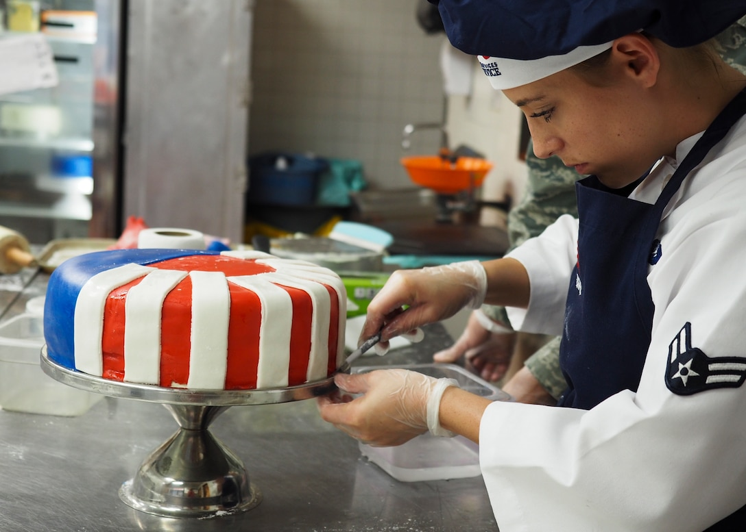 Airman 1st Class Kendall McGovern, 99th Force Support Squadron chef, prepares a layer of fondant on the Air Force's 70th anniversary celebration cake at Nellis Air Force Base, Nevada, September 17, 2017. McGovern spent more than two hours creating fondant stars and stripes to place around the multiple layers of cake. (U.S. Air Force photo by Master Sgt. Heidi West/Released)