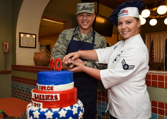 Col. Mathew Boschert, 99th Mission Support Group commander, and Airman 1st Class Rebecca Johnson, 99th Force Support Squadron chef, prepare to cut the Air Force's 70th anniversary cake at Nellis Air Force Base, Nevada, Sept. 18, 2017. The cake took more than three days to prepare, perfect and present before being served to Airmen at the Crosswinds Inn dining facility. (U.S. Air Force photo by Airman 1st Class Andrew D. Sarver/Released)