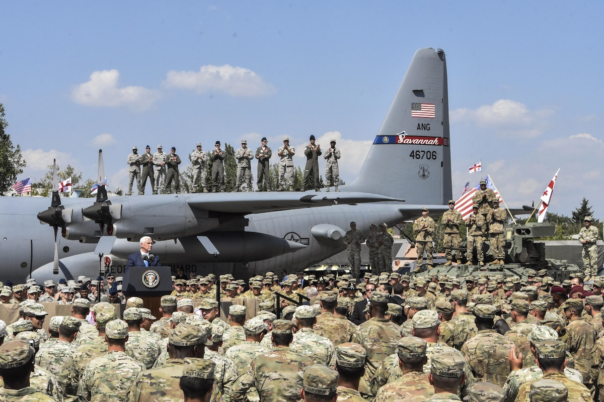 The U.S. vice president gives an address as some troops stand on an airplane's wing.