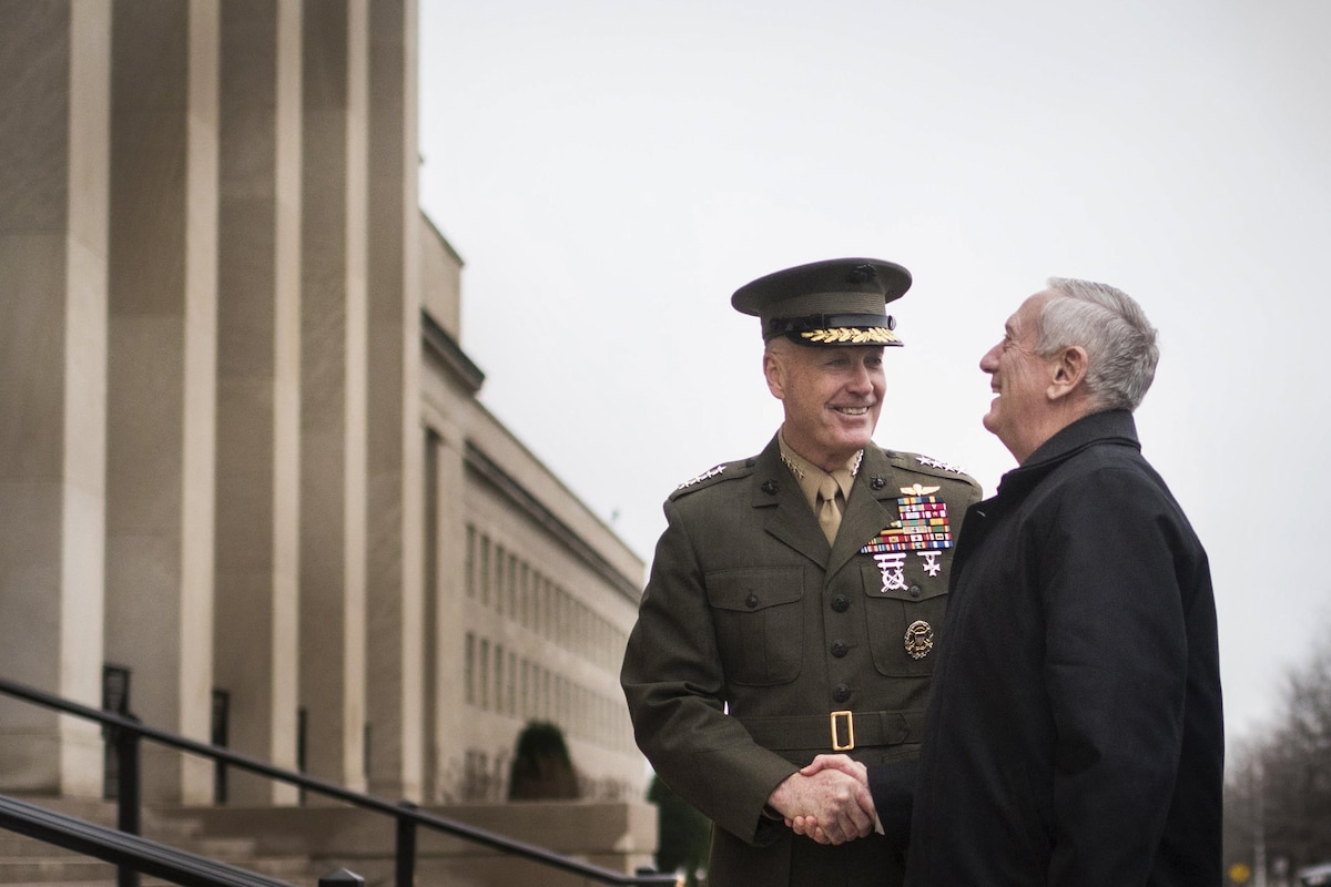 Defense Secretary James N. Mattis smiles as he shakes hands with Marine Corps Gen. Joe Dunford outside the Pentagon.