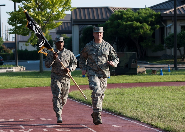 U.S. Air Force Col. David G. Shoemaker, 8th Fighter Wing commander, and Chief Master Sgt. Reiko L. Meeks, 8th FW command chief, run with the Prisoner of War and Missing in Action flag during the opening ceremony of POW/MIA Recognition Day at Kunsan Air Base, Republic of Korea, Sept. 14, 2017. Shoemaker and Meeks ran the first leg of the 24-hour run in remembrance of the POW/MIA service members. (U.S. Air Force photo by Staff Sgt. Victoria H. Taylor)