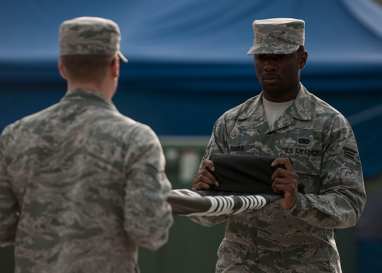 U.S. Air Force Senior Airman Ryan Harris, 8th Security Forces Squadron defender, folds the POW/MIA flag during the closing ceremony of the POW/MIA Recognition Day at Kunsan Air Base, Republic of Korea, Sept. 15, 2017.  The day was established by an Act of Congress, by the passage of Section 1082 of the 1998 Defense Authorization Act and is one of six days that the POW/MIA Flag can be flown. (U.S. Air Force photo by Staff Sgt. Victoria H. Taylor)