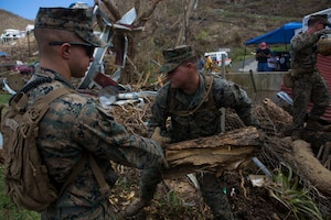U.S. Marine Corps Sgt. Austin C. Morgan, an assaultman with Battalion Landing Team 2nd Battalion, 6th Marine Regiment, 26th Marine Expeditionary Unit (MEU), to clear debris at a local fire station that was affected by Hurricane Irma in St. John, U.S. Virgin Islands, Sept. 17, 2017.
