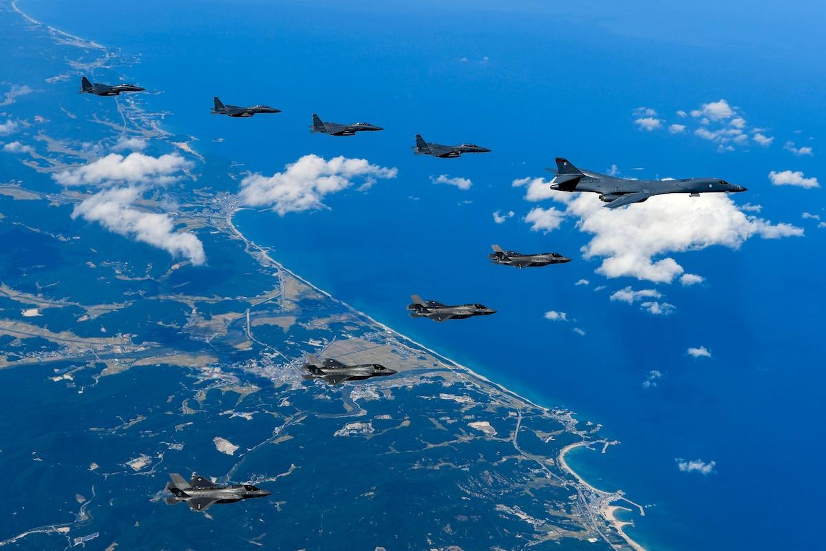 "Nine aircraft fly over coastline in a ""V"" formation."
