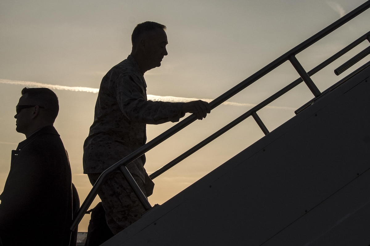 Marine Corps Gen. Joe Dunford, chairman of the Joint Chiefs of Staff, shown in silhouette, climbs the stairs to an aircraft.