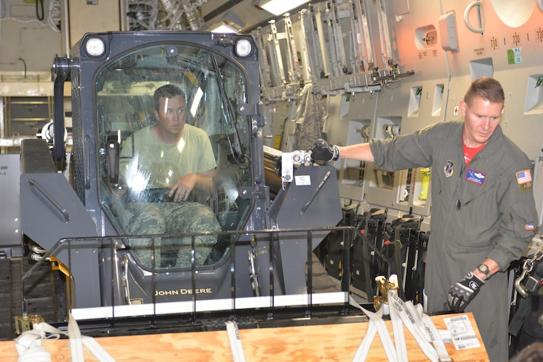 U.S.  Air Force Staff Sgt. Travis Albee, Air Transportation Craftsman, 157th Logistics Readiness Squadron, New Hampshire Air National Guard, operates a skid steer as Master Sgt. Brian Hamilton, Loadmaster, 183rd Airlift Wing, Mississippi Air National Guard, guides him onto a C-17A Globemaster. The skid steer is part of the Disaster Relief Bed Down Kit (DRBS) deploying from Pease ANGB. to the Virgin Islands in support of the Irma relief effort.  The DRBS kit is one of two kits stored here at Pease Air National Guard Base.  (N.H. Air National Guard Photo by Master Sgt. Thomas Johnson)