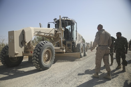 U.S. Marine Gunnery Sgt. Ronnie Mills, a route clearance advisor with Task Force Southwest, observes as an Afghan National Army engineer soldier with 215th Corps levels a road using a Caterpillar 120M Motor Grader at Camp Shorabak, Afghanistan, Sept. 18, 2017. More than 20 soldiers assigned to various engineer kandaks throughout Helmand province are executing a five-week Heavy Equipment Maintenance Operator Course, which is designed to improve the soldiers' route clearance skills and develop their technical abilities using large vehicles. (U.S. Marine Corps photo by Sgt. Lucas Hopkins)