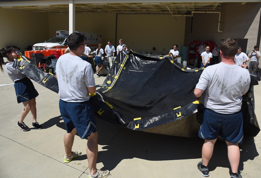 Members of the 81st Medical Group assemble a decontamination tent during the 81st MDG integrated in-place patient decontamination training course behind the Keesler Medical Center Sept. 14, 2017, on Keesler Air Force Base, Mississiippi. The two-day course trained 21 personnel, which came from four different disaster medical teams: IPPD , triage, manpower and security. Throughout the training, they learned to utilize Keesler's fixed decontamination facility and how to set up and tear down the decontamination tent. (U.S. Air Force photo by Kemberly Groue)