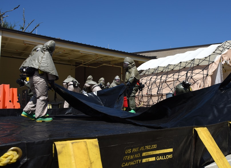 Members of the 81st Medical Group assemble a decontamination tent during the 81st MDG integrated in-place patient decontamination training course behind the Keesler Medical Center Sept. 14, 2017, on Keesler Air Force Base, Mississippi. The two-day course trained 21 personnel, which came from four different disaster medical teams: IPPD, triage, manpower and security. Throughout the training, they learned to utilize Keesler's fixed decontamination facility and how to set up and tear down the decontamination tent. (U.S. Air Force photo by Kemberly Groue)