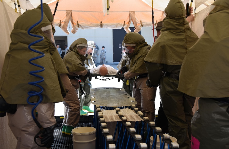 """Members of the 81st Medical Group move a """"patient"""" through a decontamination tent during the 81st MDG integrated in-place patient decontamination training course behind the Keesler Medical Center Sept. 14, 2017, on Keesler Air Force Base, Mississippi. The two-day course trained 21 personnel, which came from four different disaster medical teams: IPPD, triage, manpower and security. Throughout the training, they learned to utilize Keesler's fixed decontamination facility and how to set up and tear down the decontamination tent. (U.S. Air Force photo by Kemberly Groue)"""