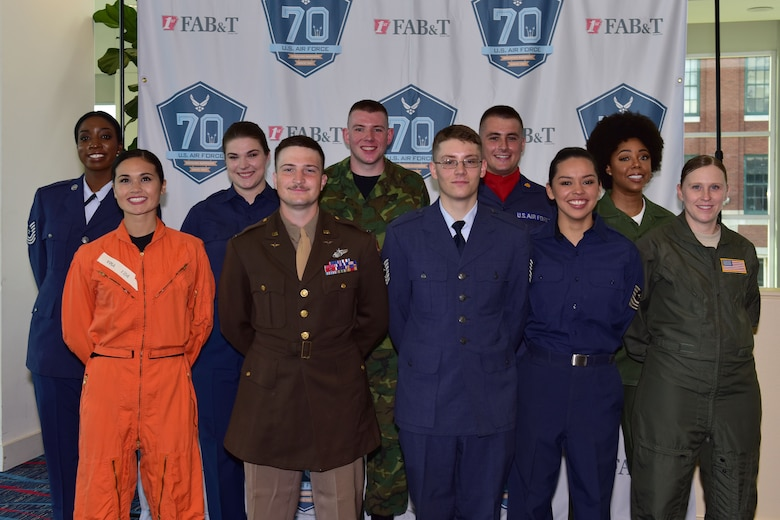 A group of people stand in front of a background wearing different historic U.S. Air Force uniforms.