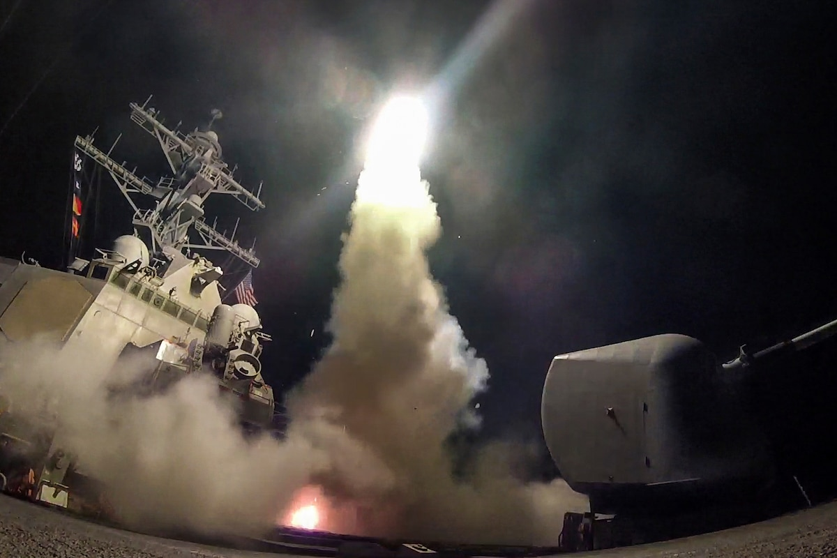 A destroyer launches a missile at night, creating smoke and light.