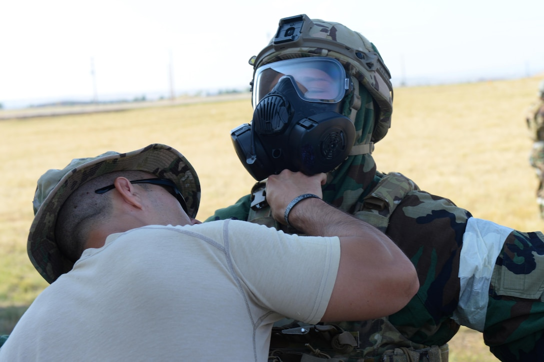 Senior Airman Parker Davis, an explosive ordnance disposal technician assigned to the 28th Civil Engineer Squadron, is inspected by Master Sgt. Carlos Sanchez, the EOD section chief assigned to the 28th CES, during an EOD Team of the Year competition at Ellsworth Air Force Base, S.D., Sept. 12, 2017. The chemical scenario during the event simulated the need for a leak seal and package in a decontamination line. (U.S. Air Force photo by Airman Nicolas Z. Erwin)