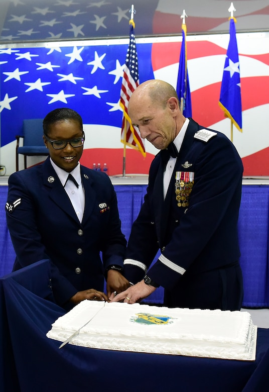 Gen. Mike Holmes, right, commander of Air Combat Command, and Airman 1st Class Deja Adams, left, 4th Logistics Readiness Squadron flight service center apprentice, cut a cake during the the 4th Fighter Wing 75th Anniversary Gala, Sept. 16, 2017, at Seymour Johnson Air Force Base, North Carolina. The cake cutting tradition calls for the oldest and youngest Airman present to use a saber to cut the cake together. (U.S. Air Force photo by Airman 1st Class Victoria Boyton)