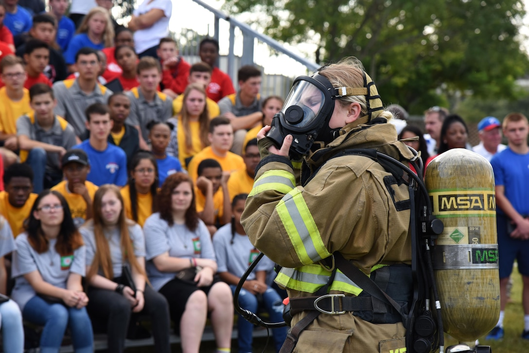 Airman 1st Class Hannah Reichert, 81st Infrastructure Division firefighter, demonstrates how to quickly put on firefighter gear at the Science, Technology, Engineering and Mathematics Diversity Outreach Day Sept. 15, 2017, on Keesler Air Force Base, Mississippi. The event consisted of 10 Mississippi gulf coast high school Junior ROTC units viewing an 81st Security Forces Squadron military working dog demonstration and receiving information about Air Force opportunities and accession requirements with an emphasis on STEM. They also competed in several team building activities. (U.S. Air Force photo by Kemberly Groue)