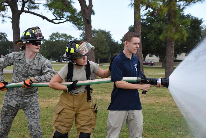Staff Sgt. Codee Potts, and Airman 1st Class Hannah Reichert, 81st Infrastructure Division firefighters, assist Riley McElfish, Bay High School Junior ROTC cadet, with operating a fire hose at the Science, Technology, Engineering and Mathematics Diversity Outreach Day Sept. 15, 2017, on Keesler Air Force Base, Mississippi. The event consisted of 10 Mississippi gulf coast high school Junior ROTC units viewing an 81st Security Forces Squadron military working dog demonstration and receiving information about Air Force opportunities and accession requirements with an emphasis on STEM. They also competed in several team building activities. (U.S. Air Force photo by Kemberly Groue)